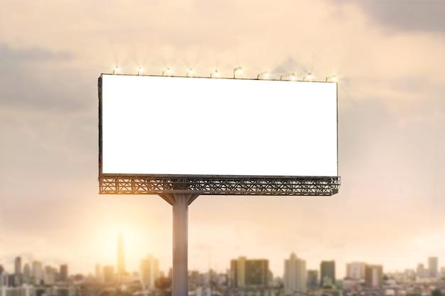 Cartelera en blanco para el anuncio sobre fondo puesta de sol de la ciudad