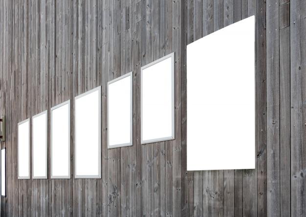 Cartelera en blanco blanca del anuncio en el fondo de madera oscuro de la pared