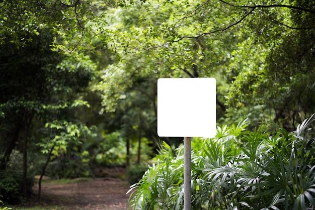 Cartelera en blanco blanca en el parque con el fondo de la naturaleza.