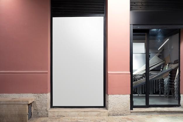 Cartelera en blanco blanco cerca de la entrada.
