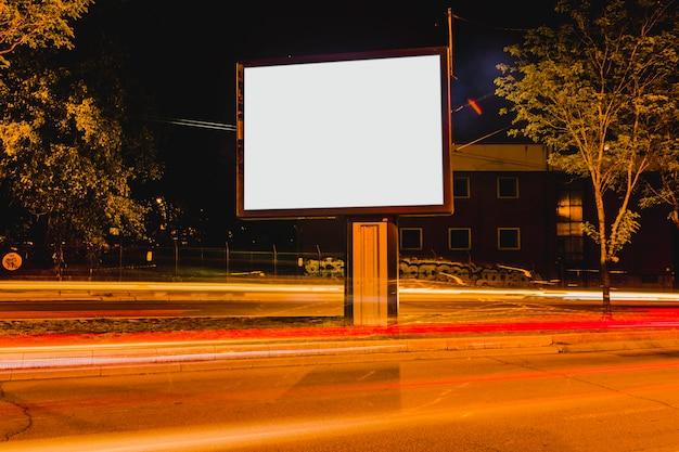 Cartelera en blanco blanco con semáforos borrosos en la carretera
