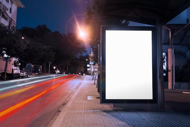Cartelera en blanco en la parada de autobús por la noche con las luces de los autos pasando por