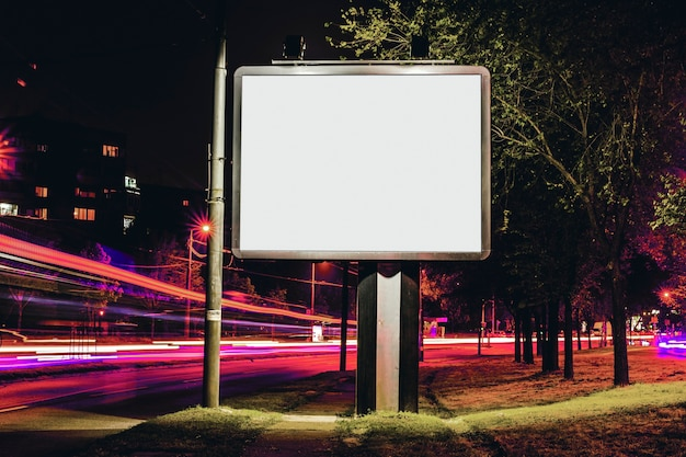Cartelera en blanco para publicidad exterior con luz en el fondo.