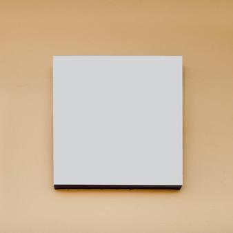 Cartelera de forma cuadrada blanca sobre fondo beige