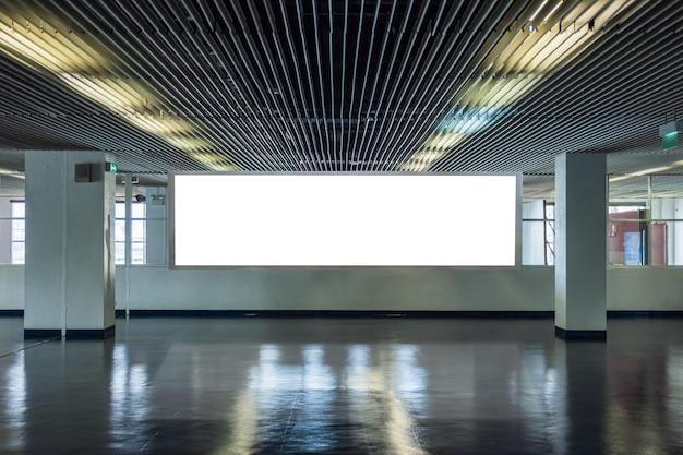 Cartelera grande en pasillo de diseño metálico con ventanas transparentes.