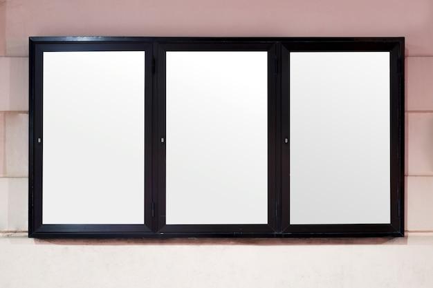 Cartelera de publicidad en blanco blanco con borde negro en la pared