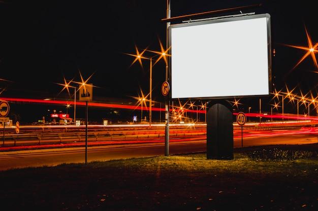 Cartelera de publicidad en blanco con semáforos borrosos en la noche