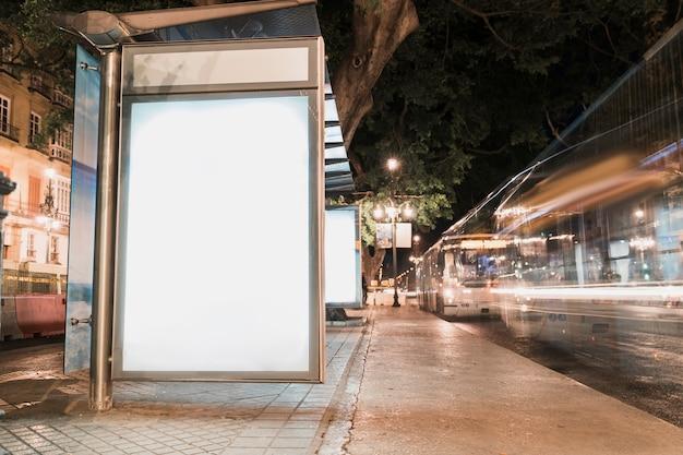 Cartelera publicitaria en blanco en la parada de autobús con semáforos borrosos