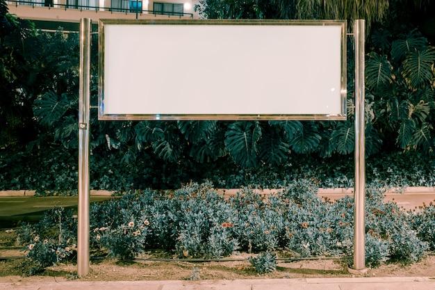 Cartelera rectangular en blanco en el jardín.