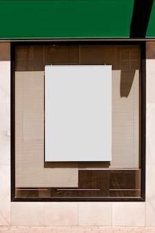 Cartelera rectangular en blanco en ventana de vidrio con persianas