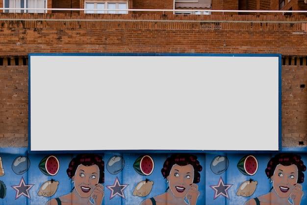 Cartelera rectangular en pared de ladrillo con graffiti.