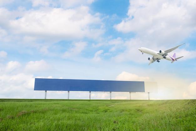 Cartelera sobre hierba verde con fondo de cielo azul y avión