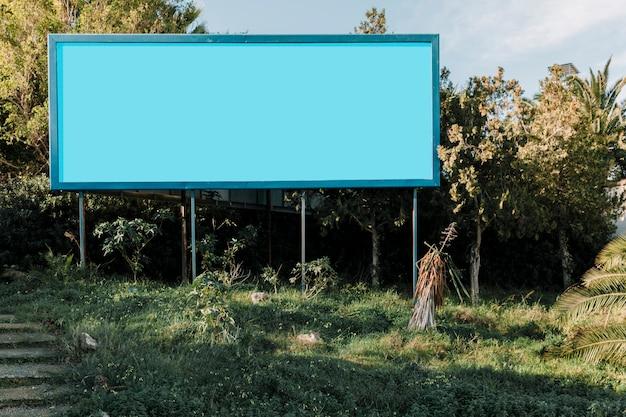 Cartelera vacía azul en prado verde