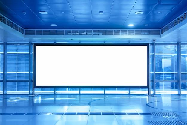Cartelera vacía en blanco dentro de un centro comercial o metro subterráneo en dubai, emiratos árabes unidos. tonos azules