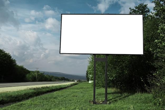 Cartelera vacía para cartel publicitario cerca de carretera asfaltada y bosque verde, sobre fondo de cielo azul.