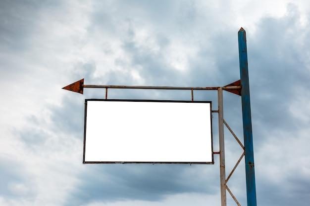 Cartelera vacía vieja para el cartel publicitario con el signo de la flecha en el fondo del cielo nublado lluvioso.