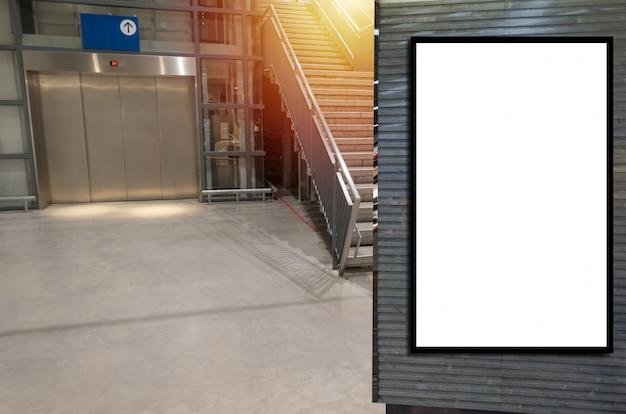 Cartelera vertical en blanco o caja de luz publicitaria n frente al elevador y escaleras en el centro comercial de grandes almacenes