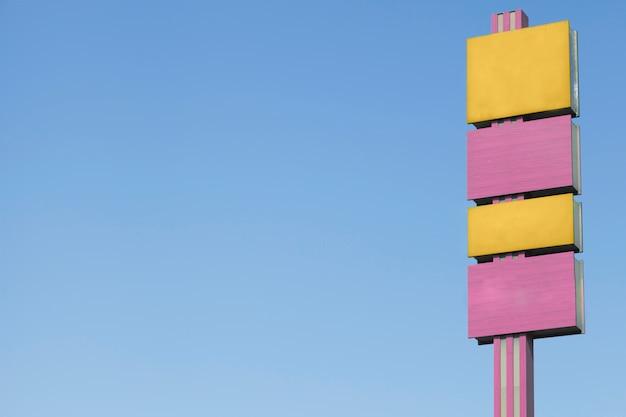 Carteles publicitarios amarillos y rosados contra el cielo azul.