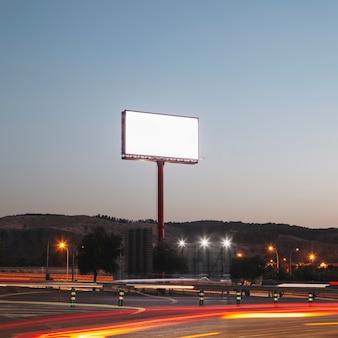 Carteles publicitarios en blanco en la carretera iluminada por la noche