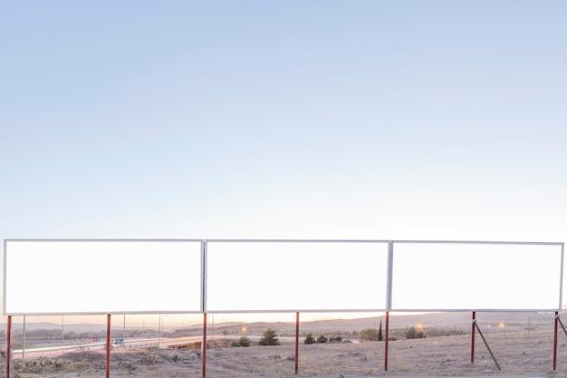 Carteles publicitarios en blanco cerca de la carretera contra el cielo azul