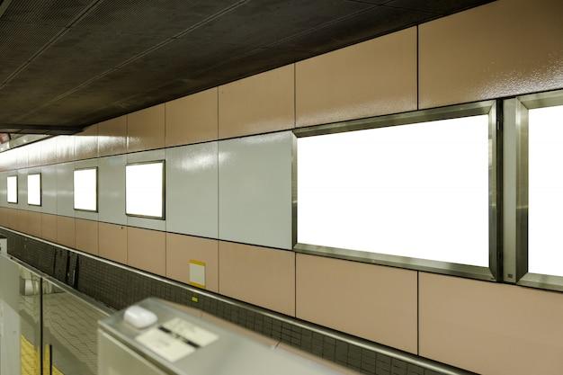 Carteles publicitarios en blanco colocados en la pared del metro.