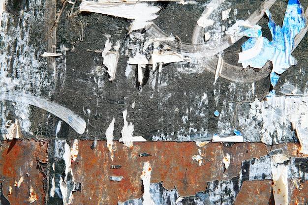 Carteles rotos en una pared.