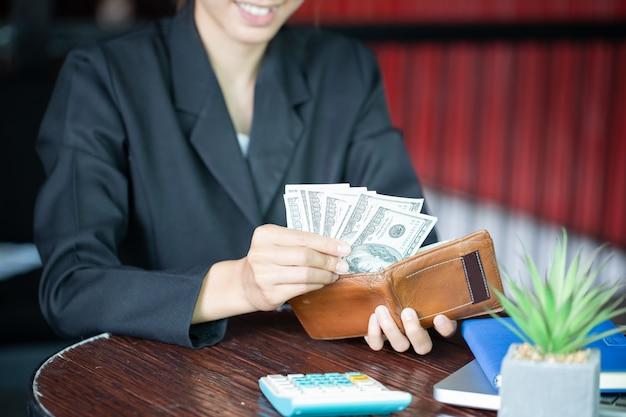 Cartera de cuero con dinero en manos femeninas sobre fondo oscuro