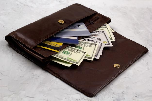 Cartera de cuero marrón abierta llena de dólares y tarjetas de crédito.