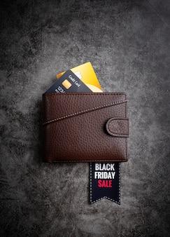 Cartera de cuero marrón con texto black friday sale en una etiqueta y tarjetas de crédito