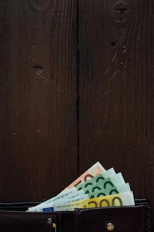 Cartera marrón con billetes en euros en la mesa de madera