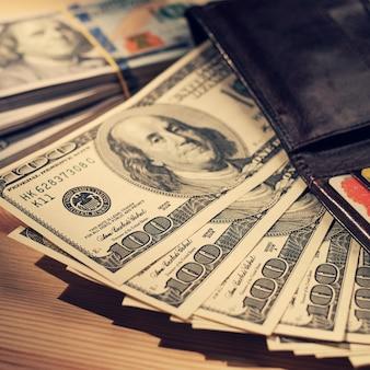 Cartera marrón con tarjetas de crédito y billetes de dólar sobre madera.