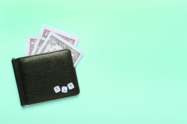 Cartera negra sobre un fondo de menta pastel con la palabra impuesto de letras de madera. vista superior, minimalismo