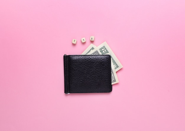 Cartera negra sobre un fondo rosa con la palabra impuesto de letras de madera. vista superior, minimalismo