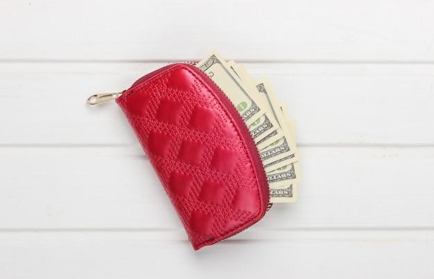 Cartera roja con billetes de cien dólares en madera blanca.