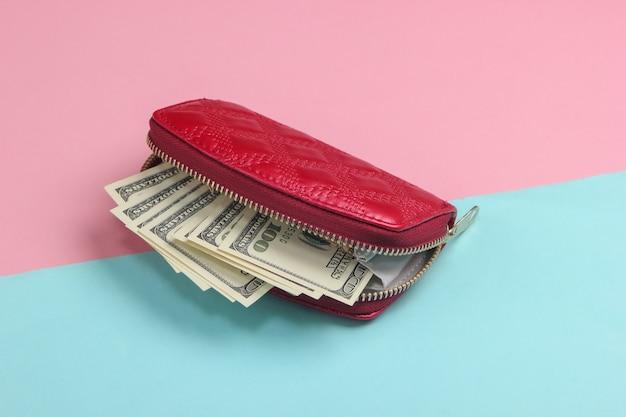 Cartera roja con billetes de cien dólares sobre un pastel azul-rosa.