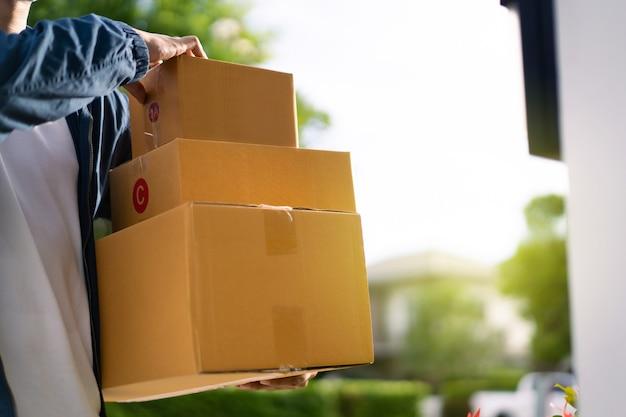 Cartero asiático con una mascarilla protectora de higiene recogiendo un paquete o una caja del camión para entregarlo en la puerta del cliente.