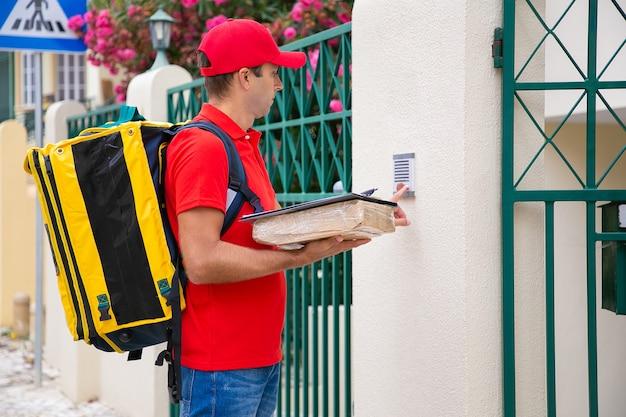 Cartero concentrado tocando el timbre y sosteniendo el paquete y el portapapeles. mensajero guapo en uniforme rojo con mochila, de pie al aire libre y entregando orden. servicio de entrega y concepto de correo.