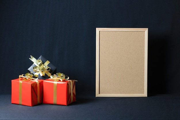 Cartón de corcho y cajas de regalo de navidad con espacio de copia aislado sobre un fondo oscuro
