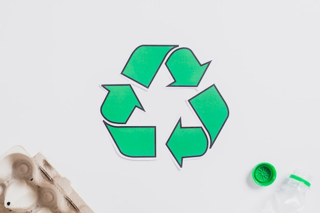 Cartón de huevos y botella de plástico con icono de reciclaje verde sobre fondo blanco