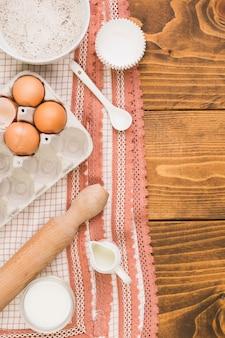 Carton de huevos; cuenco de harina; jarra de leche; rodillo; molde de muffin y cuchara en tela de diseñador sobre superficie texturizada