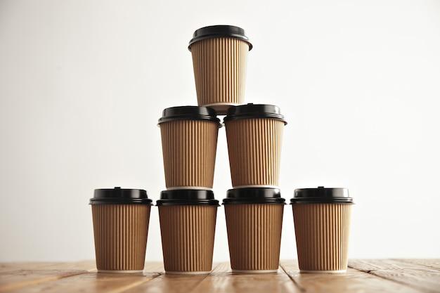 Cartón marrón para llevar vasos de papel con tapas negras en forma de casa piramidal en una mesa rústica de época en el centro de la imagen