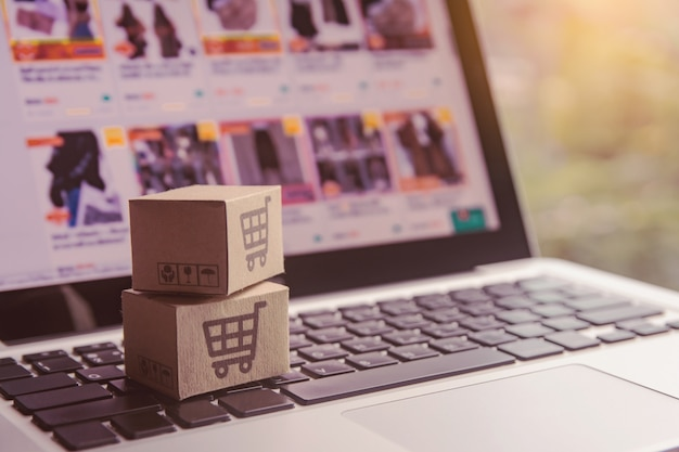 Cartones de papel con el logotipo de un carrito de compras en un teclado portátil.