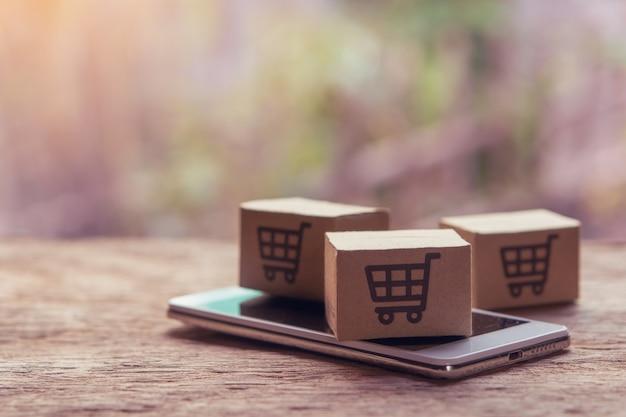 Cartones de papel con el logotipo de un carrito de compras y un teléfono inteligente en la mesa de madera.