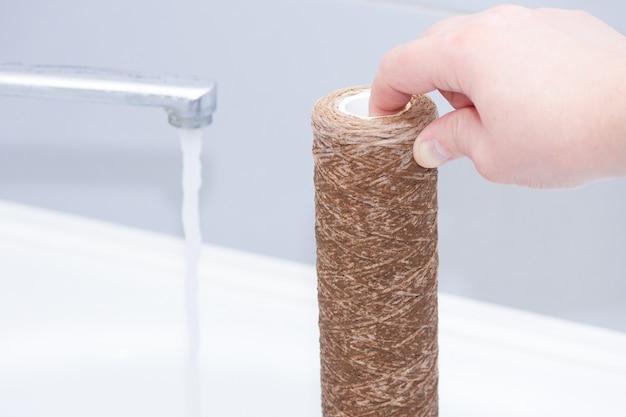 Cartucho de filtro de agua sucia usado. sistema de ósmosis de agua doméstica en la cocina.