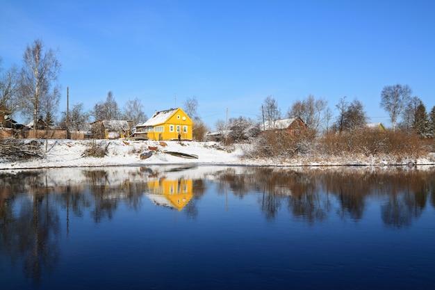 Casa amarilla en la costa del río