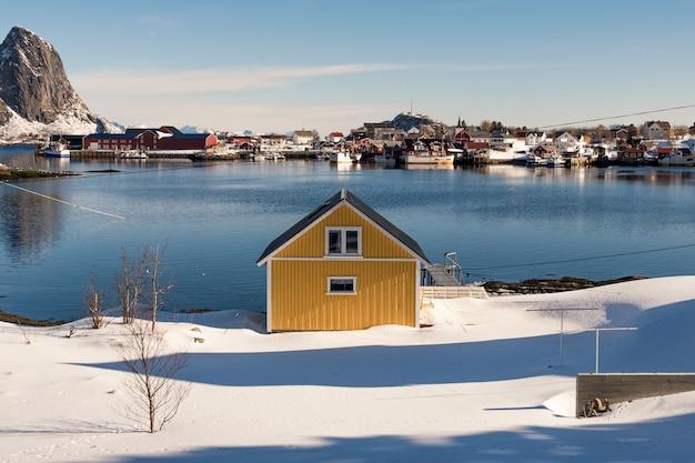 Casa amarilla sobre nieve en pueblo de pescadores