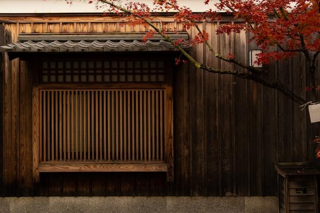 Casa antigua de japón, pared de madera y ventana con el árbol meple y la hoja roja.