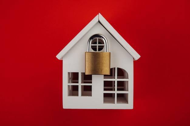 Casa blanca con cerradura cerrada. concepto de alarma y seguridad.