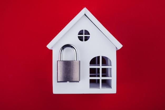 Casa blanca con cerradura cerrada sobre fondo rojo.