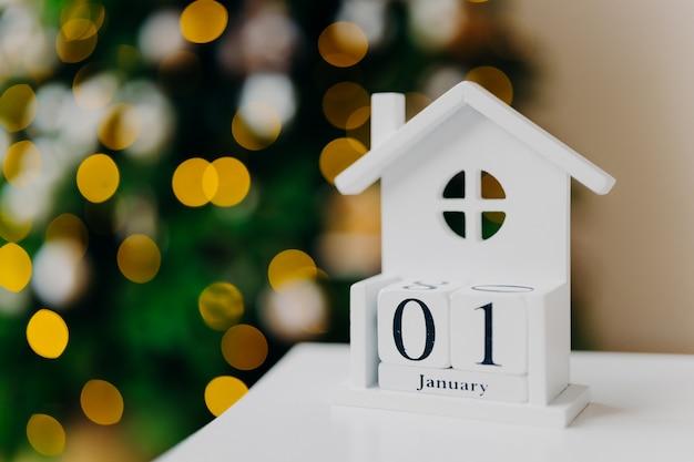 Casa blanca creativa con fecha escrita y árbol de navidad con luces. primero de enero. feliz año nuevo, concepto